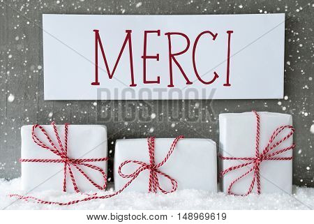 Label With French Text Merci Means Thank You. Three Christmas Gifts Or Presents On Snow. Cement Wall As Background With Snowflakes. Modern And Urban Style.