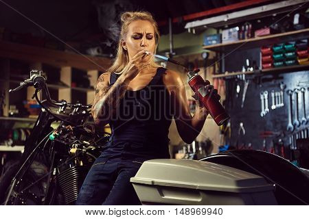 Woman mechanic lights up a cigarette with a gas burner in a motorcycle workshop