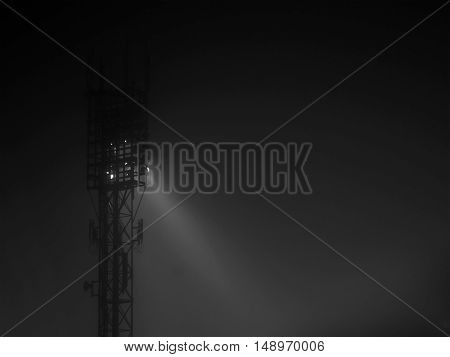 Stadium spotlights tower at night in a fog with flood of light