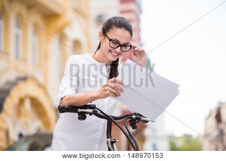 Live with positivity. Joyful delighted beautiful woman holding papers and standing near bicycle while expressing gladness