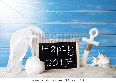 Chalkboard With English Text Happy 2017. Blue Wooden Background. Sunny Summer Card With Holiday Greetings. Beach Vacation Symbolized By Sand, Flip Flops, Anchor And Shell.