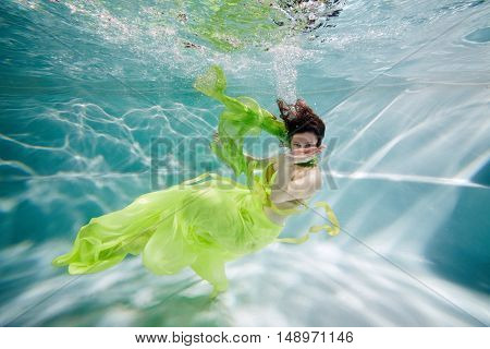 Smiling young woman in yellow-green dress swims posing in swimming pool underwater.
