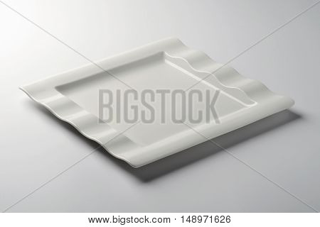 Empty Square white plate with corrugated board on white table