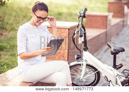 Positive way of life. Joyful beautiful glad sitting in the street and holding glasses while using tablet