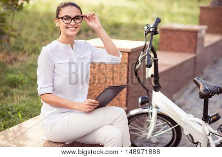 Rise your mood. Positive beautiful delighted woman holding tablet and sitting in the street while resting