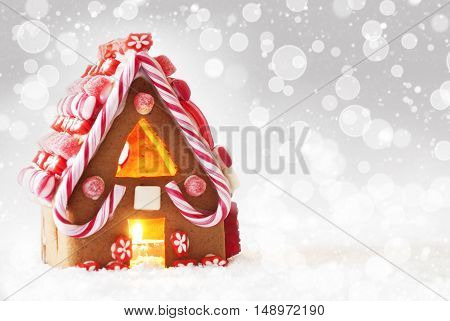 Gingerbread House In Snow As Christmas Decoration. Candlelight For Romantic Atmosphere. Silver Background With Bokeh Effect And Snowflakes. Copy Space For Advertisement