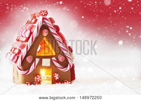 Gingerbread House In Snow As Christmas Decoration. Candlelight For Romantic Atmosphere. Copy Space For Advertisement. Red Background With Snowflakes