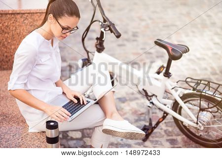 Be always in touch, Pleasant concentrated woman using laptop while sitting in the street near bicycle