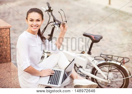 Modern way of life. Cheerful beautiful delighted woman sitting in the street and using laptop while expressing joy