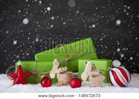 Green Gifts Or Presents With Christmas Decoration Like Moose Or Red Christmas Tree Ball. Black Cement Wall As Background With Snow. Christmas Greeting Card With Snowflakes