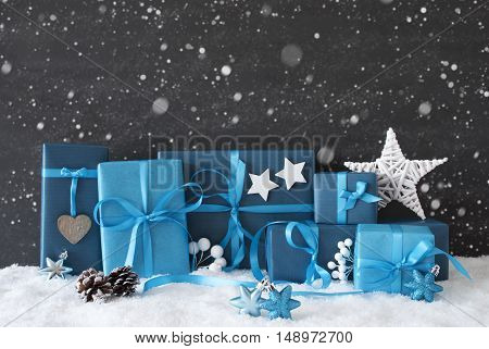Blue Gifts Or Presents With Hearts, Stars And Christmas Decoration. Black Cement Wall As Background With Snow And Snowflakes. Christmas Greeting Card For Seasons Greetings
