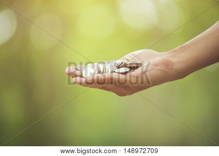 Hand With Coins On Bokeh Background .save Money Concept