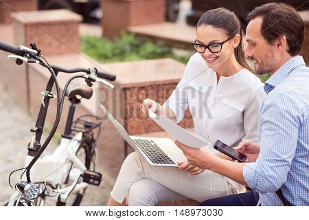 Informal communication. Positive smiling colleagues sitting in the street and using laptop while working together in the project