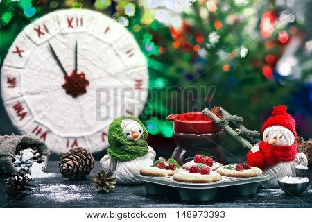 Handmade toy snowman and snowgirl of yarn skeins baking raspberry cakes over background of knitted clock and shiny Christmas decorations. Color toning