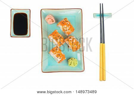 Sushi rolls with masago and soy sauce, served on turquoise plate and chopsticks over isolated white background. Top view.
