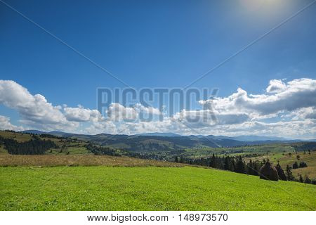 Green Meadow, Mountain And Sky With Clouds