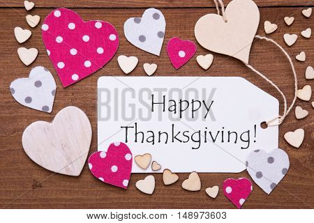 One Label With English Text Happy Thanksgiving. Flat Lay View With Wooden Vintage Background. Pink Wooden And Paper Hearts.
