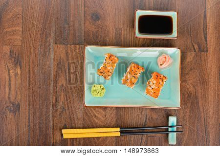 Sushi rolls with masago, served on turquoise plate with pickled ginger, soy sauce and chopsticks on wooden table. Overhead view