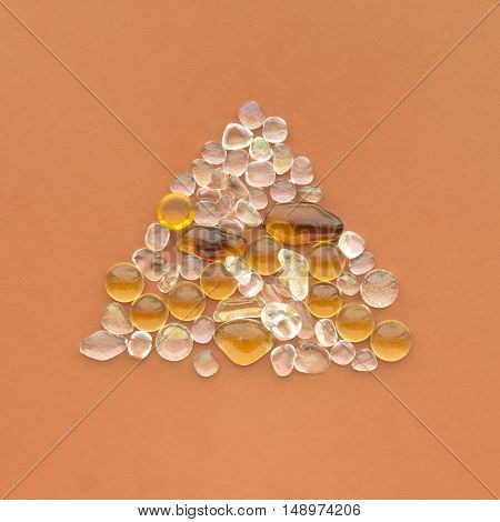 Glass pebble drops triangle decoration composition on a color paper background. Orange, amber and clear colors.