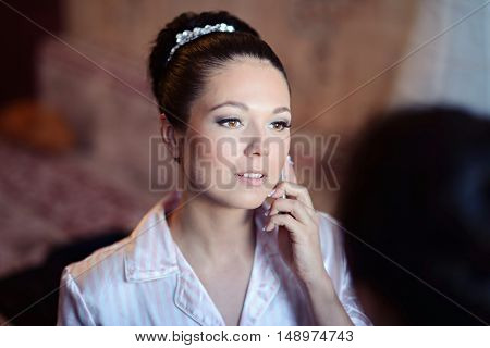 Beauty bride in dressing gown is speaking on the phone indoors. Beautiful model girl in a white wedding robe. Female portrait of cute lady. Woman with hairstyle