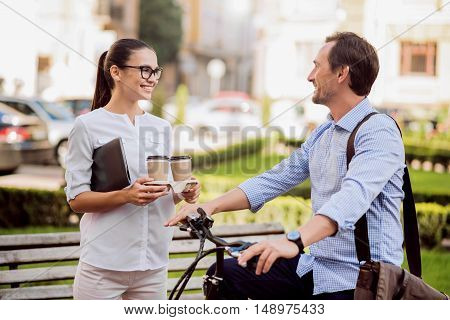 Happy day. Smiling beautiful woman holding two cups of coffee while talking to her male colleague riding on a bicycle in the park.