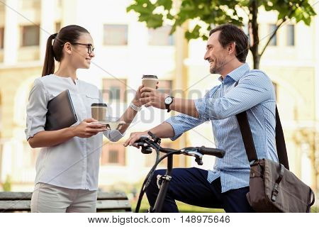 Good morning to you. Young beautiful woman giving her male colleague on a bicycle coffee before going to work while wishing him good morning.