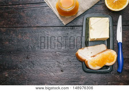 Breakfast with orange marmalade on the dark wood surface. Flat lay