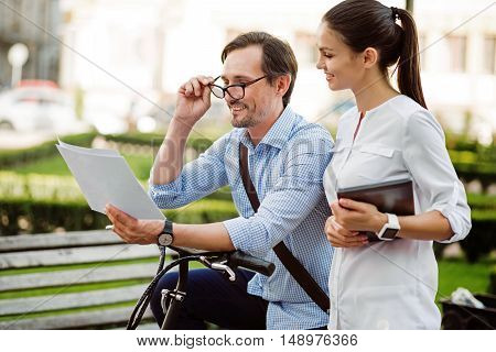 Check your results. Handsome young man reading the documents with his happy colleague while walking to their workplace