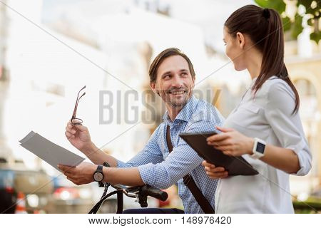 Happy to be your colleague. Young ambitious colleagues with documents and tablet enjoying each others company while going to lovely work