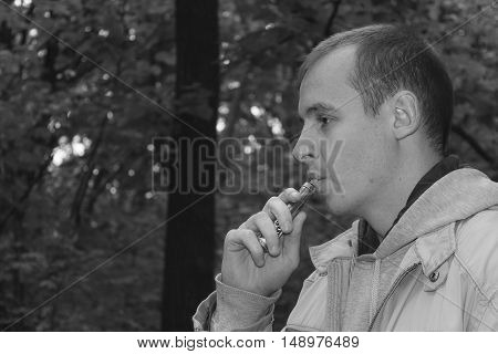 Man smoking electronic sigarette in the forest