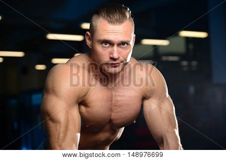 Handsome Muscular Bodybuilder Man Doing Exercises In Gym.