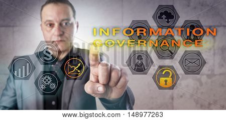 Mature IT manager activating INFORMATION GOVERNANCE onscreen. Business metaphor and technology concept for value extraction from data and reduction of organizational risk in the area of compliance.