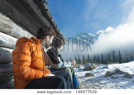 Friends is resting on wood bench in winter mountains outdoors