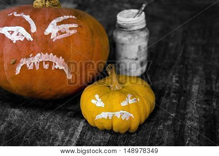 Small and large painted pumpkins next to the painting brush and bottle with colors, Halloween background, studio filtered shot