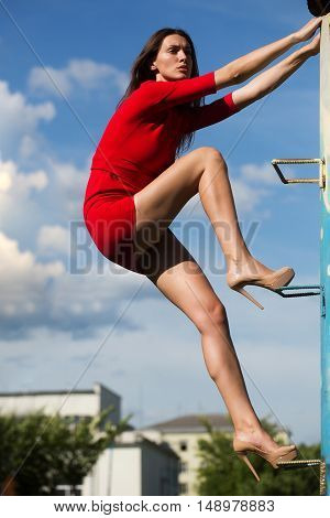 young sexy fashionable woman or girl with long brunette hair and pretty face in stylish red dress on slim body and shoes on high heels climbing on house stairs on blue sky background outdoor