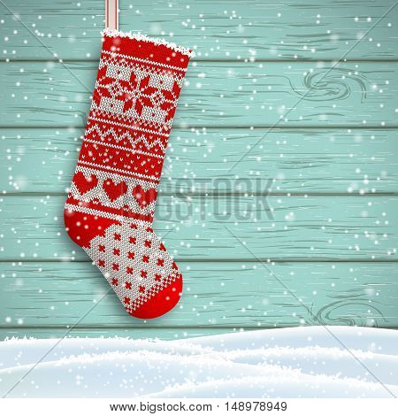 knitted christmas stocking with red patterns on blue wooden background, vector illustration, eps 10 with transparency and gradiennt meshes