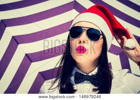 Portrait of a pretty girl in Santa Claus hat and sunglasses with bright painted lips next to striped background