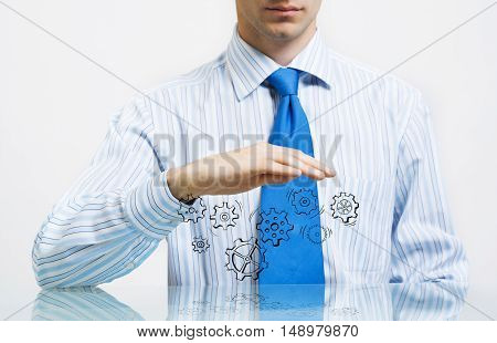 Close up of businessman sitting at table and protecting gear mechanism with palms