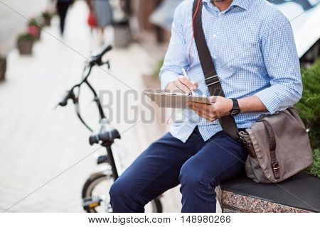 Put it down. Pleasant man sitting in the street near his bicycle and holding folder while making notes