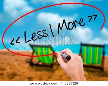 Man Hand Writing Less - More With Black Marker On Visual Screen