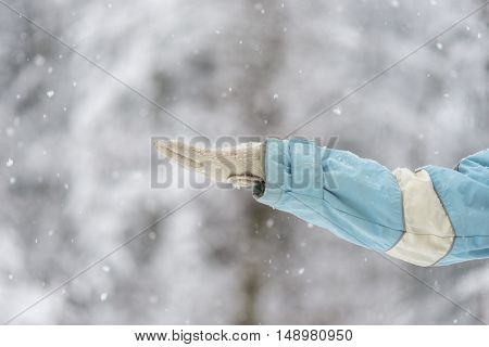 Person holding out a gloved hand to catch the snow in a wintry landscape close up view of the arm and snowflakes.