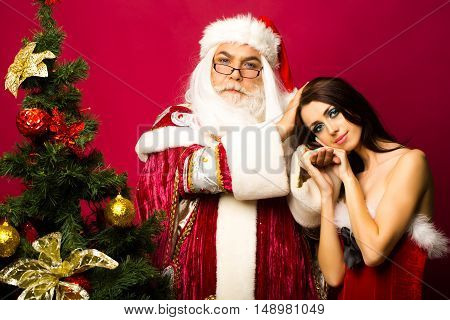 bearded santa claus man with white beard in new year coat and hat with glasses on face with pretty sexy girl or woman near decorated Christmas tree on pink background