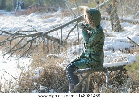 Young woman is resting in winter snowy wood with tourist thermos flask outdoors