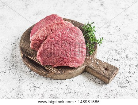 Raw beef chops and fresh thyme on a wooden cutting board on a light background
