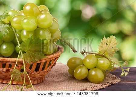 green grapes in a wicker basket on a wooden table with a blurred background.
