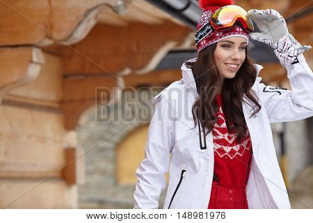 Woman skier in wooden  home terrace enjoying sun and looking at winter mountain