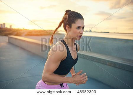 Attractive fit woman running along a promenade in the early morning training jogging across the front of the camera with a focused expression