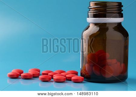 Heap of round red pills and glass pill bottle