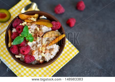 Oatmeal with berries plums nuts and honey for breakfast