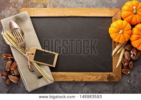Cooking and eating in fall season, forks and spoon in a rustic autumn table setting with chalkboard copyspace